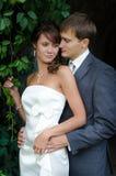 Junge Hochzeitspaare, die draußen an ihrem Hochzeitstag aufwerfen lizenzfreie stockbilder
