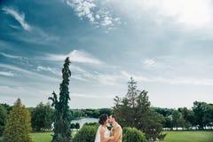 Junge Hochzeitspaare, die draußen romantische Momente genießen Stockbild