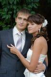 Junge Hochzeitspaare, die an ihrem Hochzeitstag aufwerfen lizenzfreies stockfoto