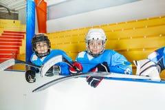Junge Hockeyspieler, die auf Bank am Stadion sitzen stockfotos