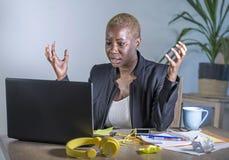 Junge hoffnungslose und betonte AfroamerikanerGeschäftsfrau, die am Laptopcomputertisch am Büroleidendruck glaubt sa arbeitet Lizenzfreie Stockbilder