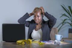 Junge hoffnungslose und betonte AfroamerikanerGeschäftsfrau, die am Laptopcomputertisch am Büroleidendruck glaubt sa arbeitet Stockbild