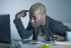 Junge hoffnungslose und betonte AfroamerikanerGeschäftsfrau, die am Laptopcomputertisch am Büroleidendruck glaubt sa arbeitet Lizenzfreies Stockfoto