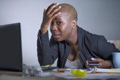 Junge hoffnungslose und betonte AfroamerikanerGeschäftsfrau, die am Laptopcomputertisch am Büroleidendruck glaubt sa arbeitet Stockbilder