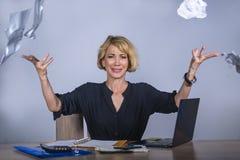 Junge hoffnungslose und betonte Geschäftsfraufunktion überwältigt am Schreibtisch mit Laptop-Computer werfender Schreibarbeit in  lizenzfreie stockbilder