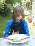 Junge Holdning eine Katze am Tisch Stockfotografie