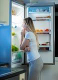 Junge hungrige Frau, die offenen Kühlschrank betrachtet und etwas wählt zu essen lizenzfreie stockfotos