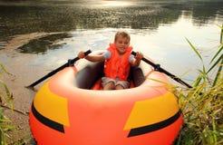 Junge im aufblasbaren Boot im Wasser stockfoto