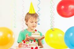 Junge im festlichen Hut mit Stück des Geburtstagskuchens Stockfoto