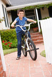 Junge im Garten mit Fahrrad Stockfotografie