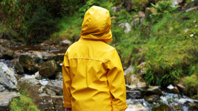 Junge im gelben Mantel passt den Fluss auf Stockfotos