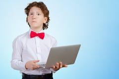 Junge im Gesellschaftsanzug mit Laptop Lizenzfreie Stockfotografie