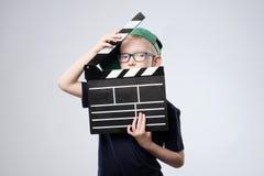 Junge im grünen Hut, der Scharnierventilbrett in den Händen hält Stockfotografie