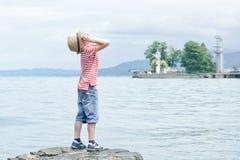 Junge im Hut, der auf dem Strand steht und oben schaut Kleines lighthous Stockfotografie