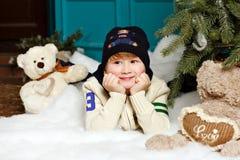 Junge im Hut lächelt und liegt auf dem Schnee in einem Studio Weihnachten lizenzfreie stockbilder