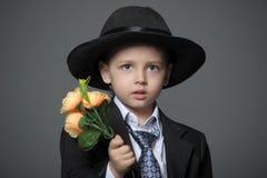Junge im Kostüm mit Blumen Stockfoto