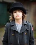 Junge im langen Mantel und im Zylinder lizenzfreie stockfotos