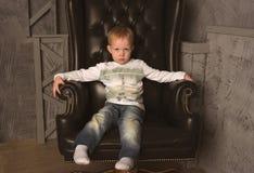 Junge im Lederstuhl Stockfotografie