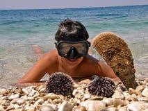 Junge im Meer, in tauchender Schablone und in Bengel, Krebs Lizenzfreie Stockfotos