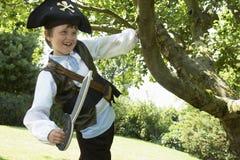 Junge im Piraten-Kostüm, das vom Baum schwingt Lizenzfreie Stockfotografie