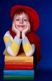 Junge im roten Barett mit bunten Büchern   Stockbild