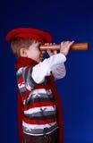 Junge im roten Schal und im Barett mit einem Spyglass Stockfoto