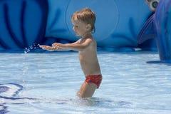 Junge im roten Schmelzen spielt mit Wasser Lizenzfreie Stockfotos