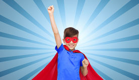 Junge im roten Superheldkap und Maske, die Fäuste zeigt stockbilder