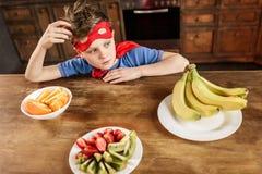 Junge im roten Superheldkostüm, das in der Küche mit Früchten sitzt Stockbild
