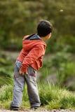 Junge im roten werfenden Stein Stockfotografie