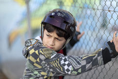 Junge im Sturzhelm durch Zaun Lizenzfreies Stockfoto