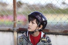 Junge im Sturzhelm durch Zaun Lizenzfreies Stockbild