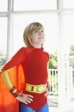 Junge im Superheld-Kostüm mit den Händen auf Hüfte Lizenzfreie Stockbilder