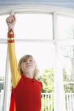 Junge im Superheld-Kostüm mit der angehobenen Faust, die oben schaut Lizenzfreies Stockfoto