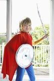 Junge im Superheld-Kostüm mit Toy Shield And Sword Lizenzfreie Stockfotos