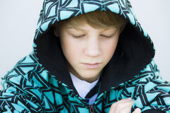 Junge im Sweatshirt, das unten schaut stockfotografie