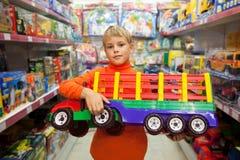 Junge im System mit großem Baumuster von LKW in den Händen Lizenzfreies Stockfoto