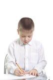 Junge im weißen Schreiben am Tisch lizenzfreies stockfoto