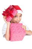 Junge im Weihnachtsroten Hut, der einen Geschenkkasten anhält Lizenzfreies Stockbild