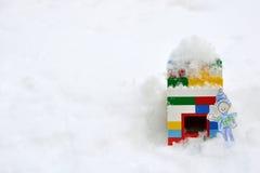 Junge im Winterschnee, der außerhalb des Blockhauses wellenartig bewegt Stockfoto