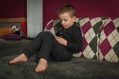 Junge im Wohnzimmer auf der Couch, die auf Tablette spielt Stockfotografie
