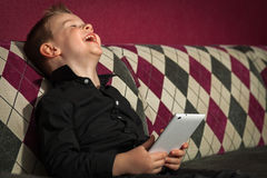 Junge im Wohnzimmer auf der Couch, die auf Tablette spielt Stockfoto