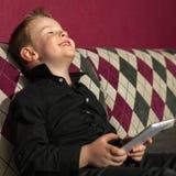 Junge im Wohnzimmer auf der Couch, die auf Tablette spielt Stockbilder
