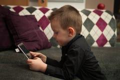 Junge im Wohnzimmer auf der Couch, die auf Tablette spielt Stockbild
