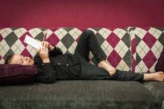 Junge im Wohnzimmer auf der Couch, die auf Tablette spielt Lizenzfreie Stockfotos