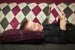 Junge im Wohnzimmer auf der Couch, die auf Tablette spielt Lizenzfreies Stockbild