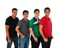 Junge indische/asiatische Gruppe von Personen, welche die Kamera, lächelnd betrachtet Lizenzfreies Stockbild