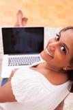 Junge indische Frau, die einen Laptop verwendet Lizenzfreie Stockfotos