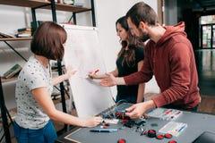 Junge Ingenieure, die elektronischen Entwurf besprechen Stockfotografie