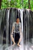 Junge innerhalb des Wasserfalles Stockfotos